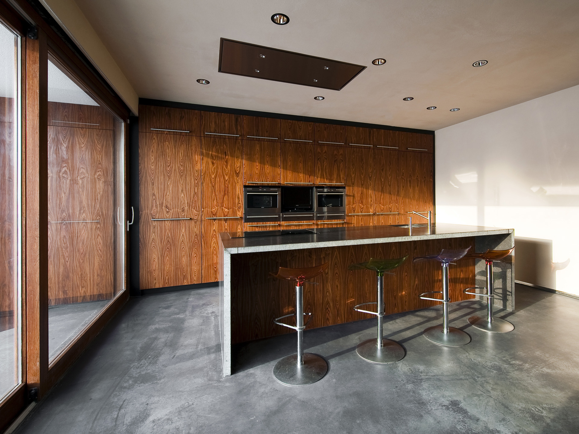 The kitchen walls have a rosewood finishing, giving the room a pure and natural feel.