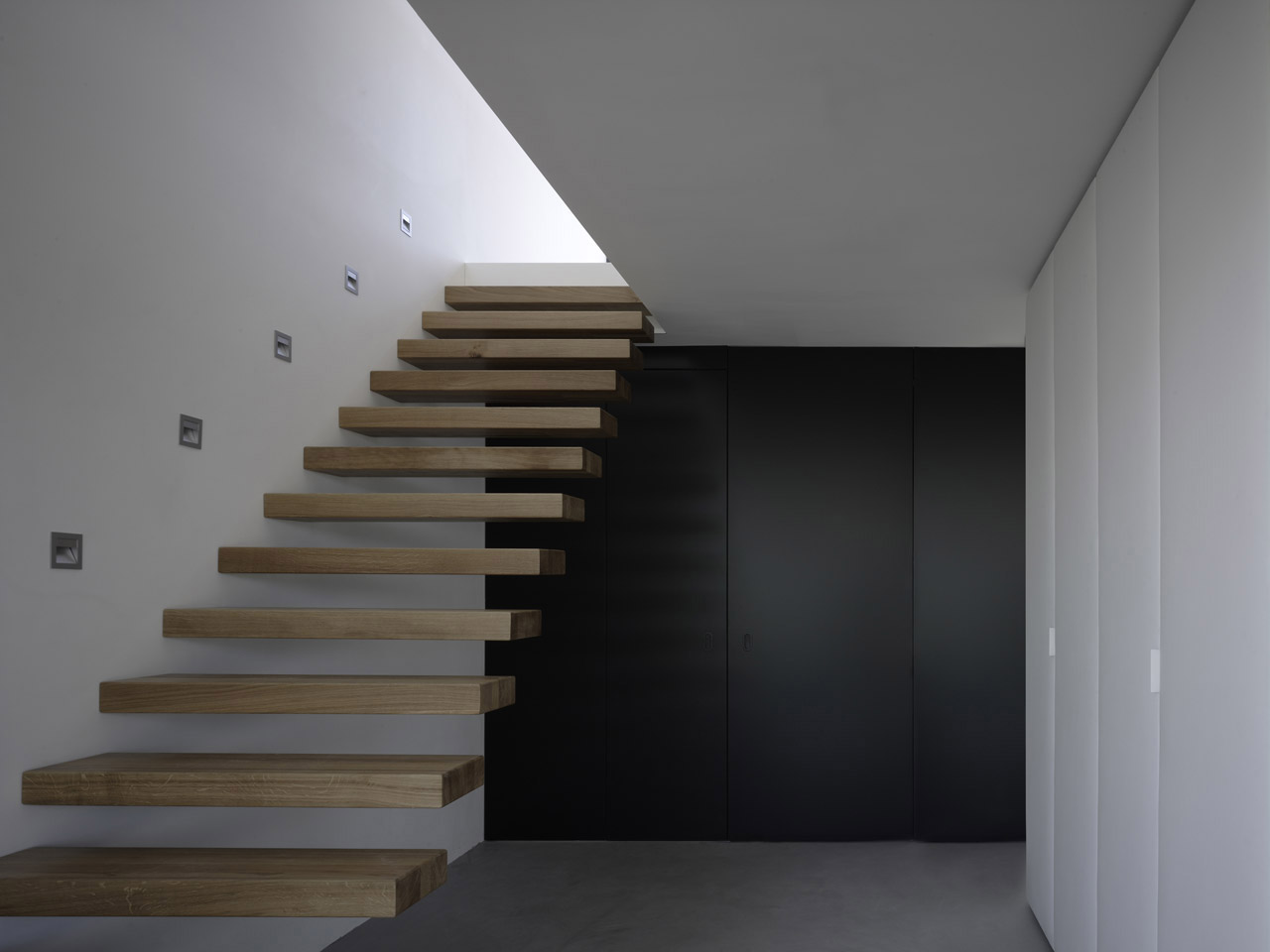 The entrance with integrated closets and floating staircase