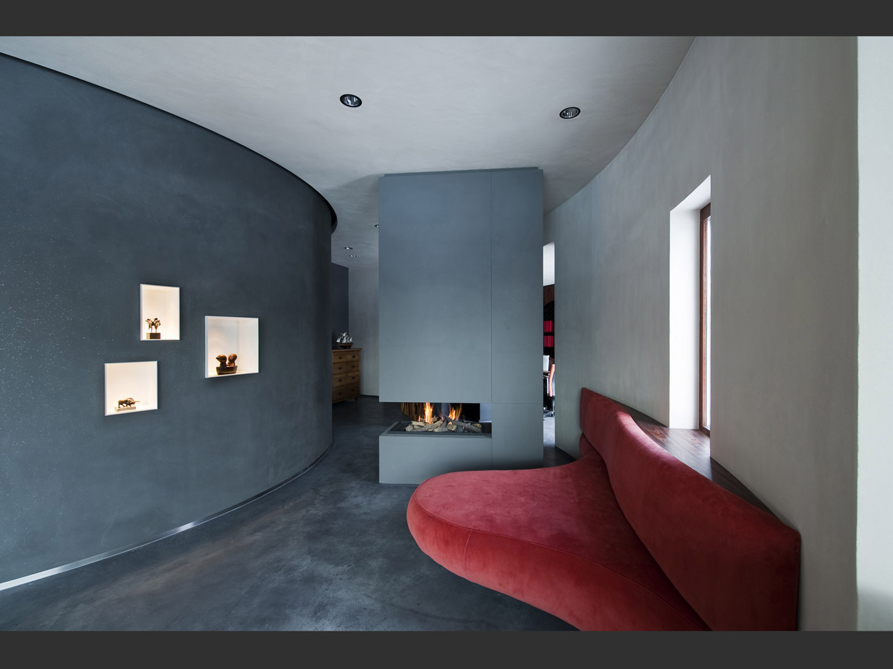 Custom made fireplace and a sofa inspired by the Mae West Lips Sofa by Salvador Dalí.